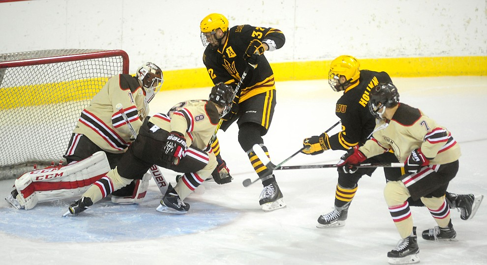 ASU's Louie Rowe puts pressure on Brown goalie Gavin Nieto as the ASU Sun Devils take on the Brown Bears from Rhode Island in the Desert Hockey Classic at the Prescott Valley Event Center Friday, December 30. (Les Stukenberg/The Daily Courier)