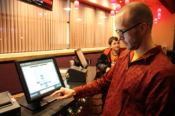 Chris Hooley selects a seat at one of Prescott Picture Show's self-service kiosks. The movie theater in Prescott has recently switched to a new system that requires customers to reserve their seats as they buy their tickets.