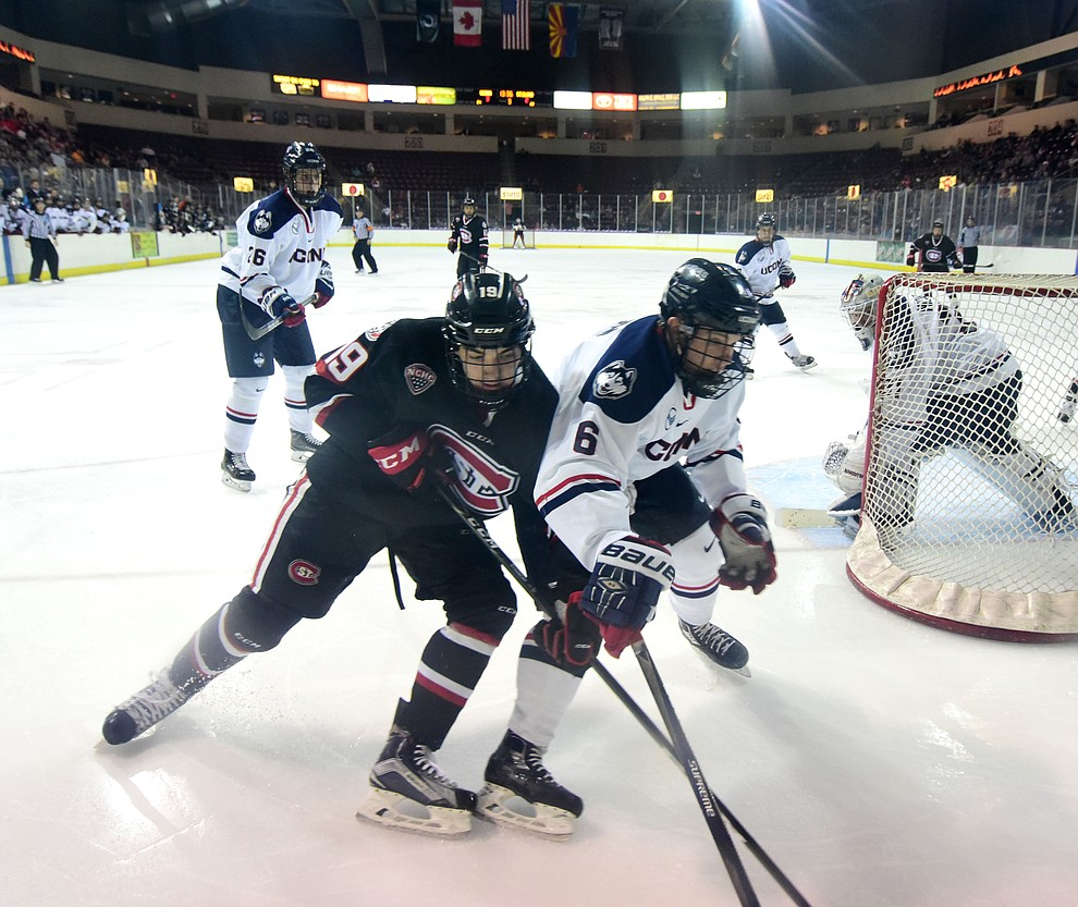 St Cloud's Mikey Eyssimont and UConn's Spencer Naas battle for the puck as the UConn Huskies take on the St Cloud State Huskies in the Desert Hockey Classic at the Prescott Valley Event Center Friday, December 30. (Les Stukenberg/The Daily Courier)