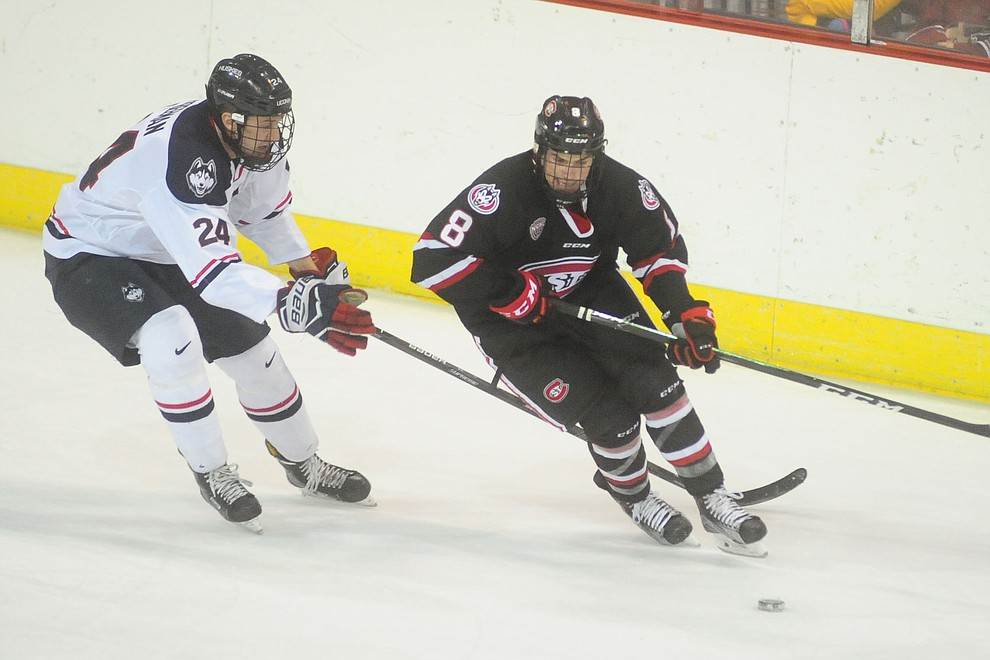 UConn's Benjamin Freeman and St CLoud's Nick Poehling go for the puck as the UConn Huskies take on the St Cloud State Huskies in the Desert Hockey Classic at the Prescott Valley Event Center Friday, December 30. (Les Stukenberg/The Daily Courier)