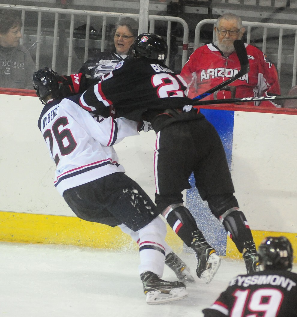 UConn's Philip Nyberg and St Cloud's Will Borgen collide into the boards as the UConn Huskies take on the St Cloud State Huskies in the Desert Hockey Classic at the Prescott Valley Event Center Friday, December 30. (Les Stukenberg/The Daily Courier)