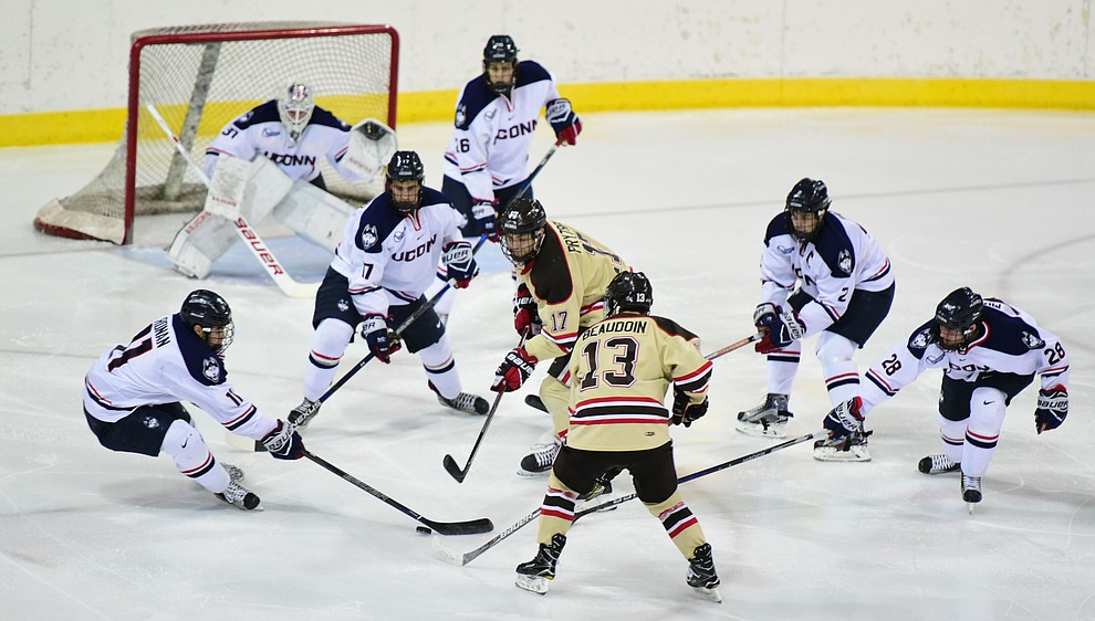 Brown's Zack Pryzbek and Brent Beaudoin are surrounded by UConn players as the Bears from Brown University take on the UConn Huskies in the championship match of the Desert Hockey Classic at the Prescott Valley Event Center Saturday, December 31. (Les Stukenberg/The Daily Courier)