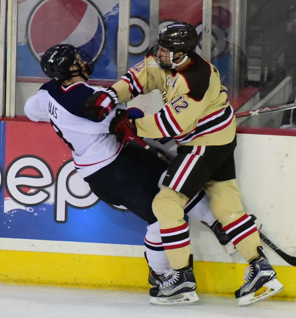 UConn's Spencer Naas takes a hard hit from Brown's Josh McArdle as the Bears from Brown University take on the UConn Huskies in the championship match of the Desert Hockey Classic at the Prescott Valley Event Center Saturday, December 31. (Les Stukenberg/The Daily Courier)