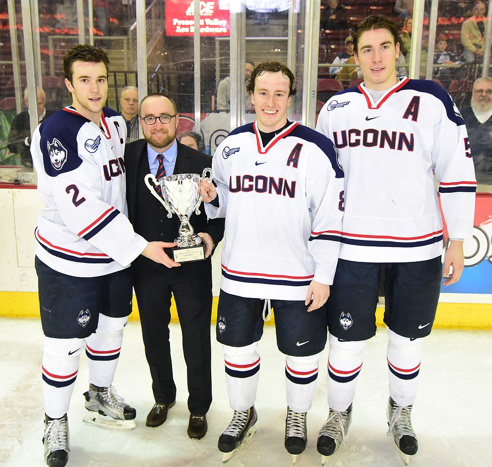 ASU Head Coach Greg Powers presents the championship trophy to the UConn Huskies after they beat the Bears from Brown University in the championship match of the Desert Hockey Classic at the Prescott Valley Event Center Saturday, December 31. (Les Stukenberg/The Daily Courier)