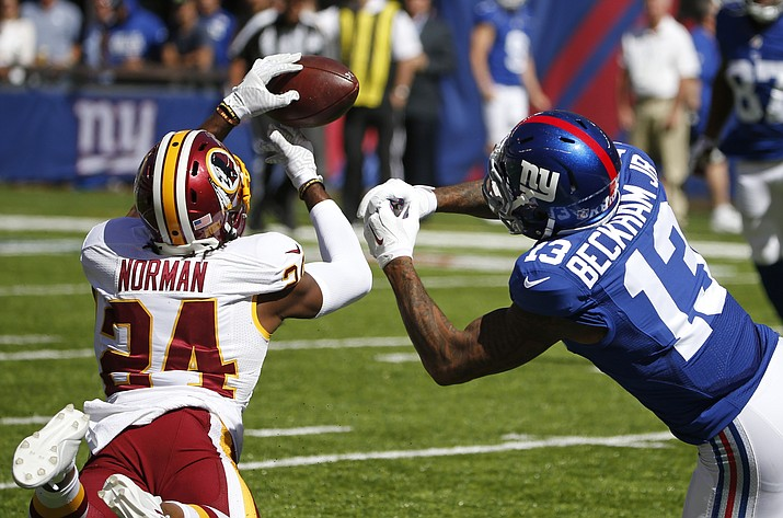 Washington Redskins cornerback Josh Norman (24) fights for control of the ball with New York Giants' Odell Beckham (13) during the first half of an NFL football game Sept. 25, 2016, in East Rutherford, N.J.