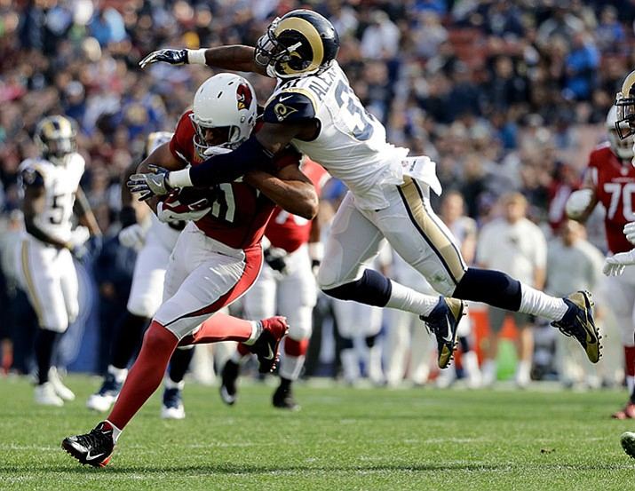 Los Angeles Rams free safety Maurice Alexander, right, tackles Arizona Cardinals wide receiver Larry Fitzgerald during the first half of an NFL football game Sunday, Jan. 1, in Los Angeles.