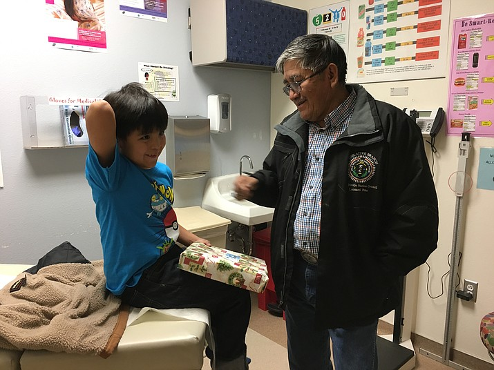 A young hospitalized boy prepares to unwrap a gift from a Navajo Nation Council delegate. Submitted photo