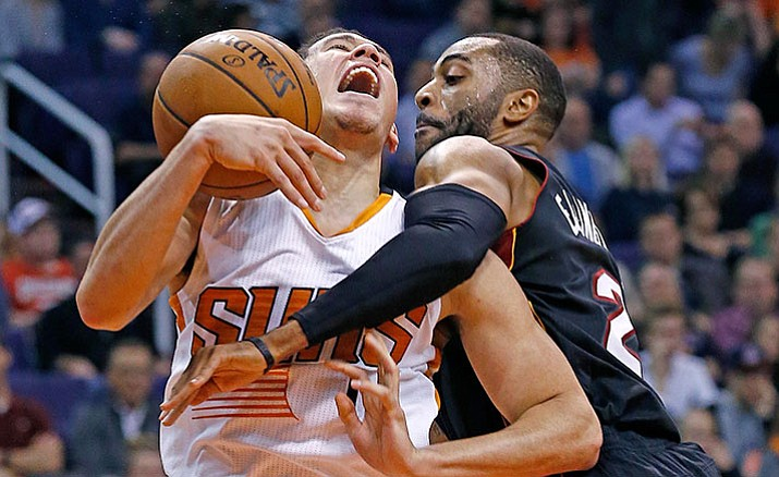 Phoenix Suns guard Devin Booker, left, gets fouled by Miami Heat guard Wayne Ellington as Booker goes up for a shot during the first half of an NBA basketball game Tuesday, Jan. 3, in Phoenix.