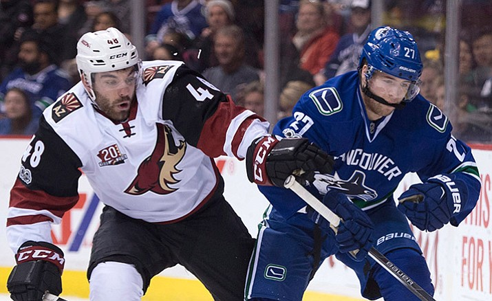 Vancouver Canucks defenseman Ben Hutton (27) fights for control of the puck with Arizona Coyotes left wing Jordan Martinook (48) during the first period of an NHL hockey game, Wednesday, Jan. 4, in Vancouver, British Columbia.
