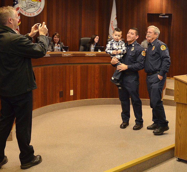 Kingman Fire Department Engineer Genaro Herrera (center) with three-year-old son Elijah pose with KFD mentor Bob Casson (right) during a badge pinning ceremony in front of City Council Tuesday.