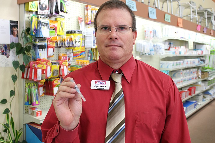 Chris Proffit holds up syringe that would administer a flu shot at Uptown Drug.