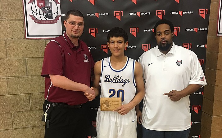 Kingman's Elijah Howery stands with tournament officials after being named to the Desert Oasis All-Tournament team. Howery and the Bulldogs host Northwest Christian at 7 p.m. Friday