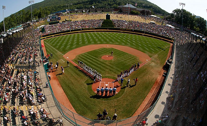 In this Aug. 28, 2016, file photo, taken with a fisheye lens, South Korea lines the third baseline and Endwell, N.Y. lines the first baseline during team introductions before the Little League World Series Championship baseball game at Lamade Stadium in South Williamsport, Pa. Little League International announced mandatory criminal background checks for its volunteer coaches, new eligibility requirements for players and a host of new rules on Wednesday, Jan. 4, 2017, intended to increase the pace of play.