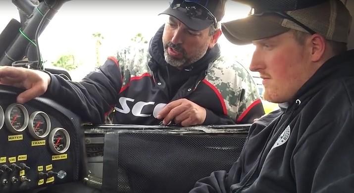 Tony Scott (left) gives instruction to veteran Matt Krumwiede on the inner workings of one of his off-road trucks.