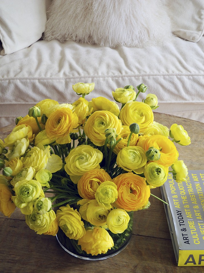 Shades of yellow are increasingly popular in home decorating and can bring a welcome burst of warmth to cooler, neutral spaces, as seen in this tabletop decorated with a vibrant yellow floral arrangement by New York-based interior designer Young Huh.