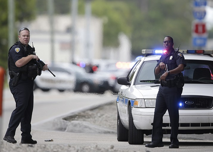 Police officers stand on the perimeter road along the Fort Lauderdale-Hollywood International Airport after a shooter opened fire inside a terminal of the airport, killing several people and wounding others before being taken into custody, Friday, Jan. 6, 2017, in Fort Lauderdale, Fla.