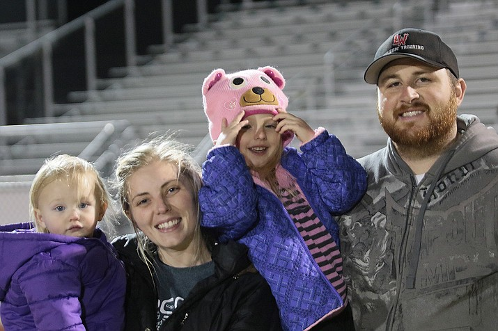 Lee Williams' athletic trainer Jess, and his wife girls' soccer coach Jessica Brinkerhoff hold their daughters as they say farewell to the fans and athletes Thursday night.