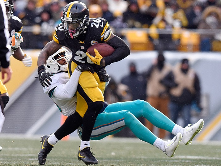Pittsburgh Steelers running back Le'Veon Bell runs through a tackle by Miami Dolphins free safety Bacarri Rambo during their  AFC wild-card game in Pittsburgh, Sunday, Jan. 8.