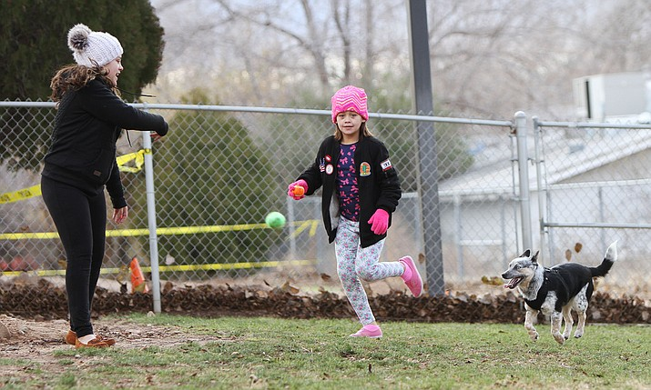 Malia, 11 (left), and Brooklyn Meador, 9, play with their dog Boy at the Lewis Kingman Dog Park Thursday. The park is one of two in the area that cater to dogs and their owners.