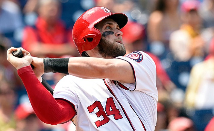 In this May 6, 2015, file photo, Washington Nationals right fielder Bryce Harper watches the ball after hitting a second home run against the Miami Marlins during the third inning of their baseball game at Nationals Park in Washington. Harper, Chicago Cubs pitcher Jake Arrieta, New York Mets pitchers Matt Harvey and Jacob deGrom, and Baltimore third baseman Manny Machado were among 146 players eligible to exchange salary arbitration figures with their teams, though most were expected to reach agreements.