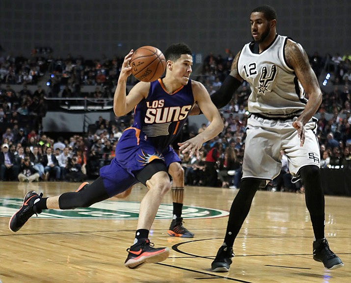 Phoenix Suns Devin Booker, left, drives the ball as San Antonio Spurs LaMarcus Aldridge attempts to block him, in the first half of their regular-season NBA basketball game in Mexico City, Saturday.