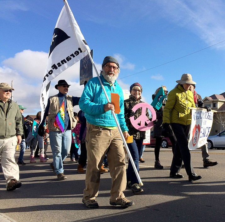 Vietnam veteran Ray Cage carries the Veterans for Peace flag, marching with 400 others for the first time in the MLK Day celebration in Prescott on Monday.