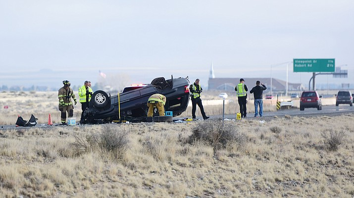 Emergency personnel check the vehicle involved in a single-vehicle rollover near the bridge at the Highway 89A and Glassford Hill Road interchange Tuesday, Jan. 17. One person was transported to YRMC by an ambulance.