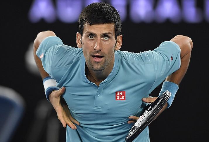 Serbia's Novak Djokovic gestures to his supporters in the crowd after defeating Spain's Fernando Verdasco in their first round match Tuesday at the Australian Open tennis championships in Melbourne, Australia. (Andy Brownbill/Associated Press)