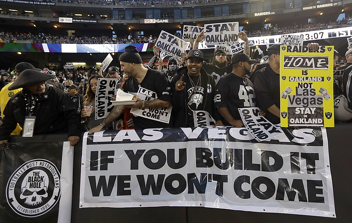 In this Nov. 6, 2016, file photo, Oakland Raiders fans hold up signs about the team's possible move to Las Vegas during an NFL football game between the Raiders and the Denver Broncos in Oakland, Calif. The Raiders have filed paperwork to move to Las Vegas. (Marcio Jose Sanchez/Associated Press, File)
