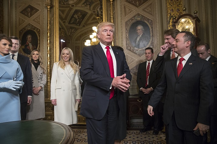 President Donald Trump leaves the President's Room of the Senate on Capitol Hill in Washington, Friday, Jan. 20, after he formally signed his cabinet nominations into law. He is joined at far left by his wife, first lady Melania Trump and daughter Tiffany Trump. At far right is Chief of Staff Reince Priebus, with White House counsel Donald McGahn, second from right.