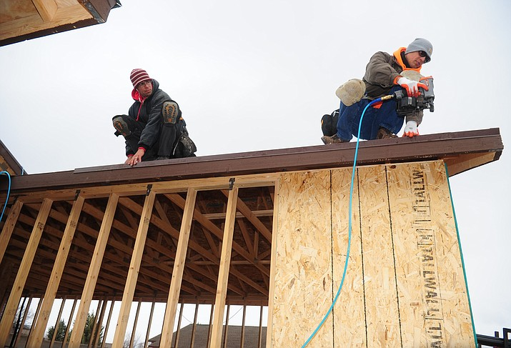 Daniel Cutter and Lorenzo Rangel of North Line Roofing work on a home in the Highlands Ranch subdivision of Chino Valley Friday, January 20. (Les Stukenberg/The Daily Courier)