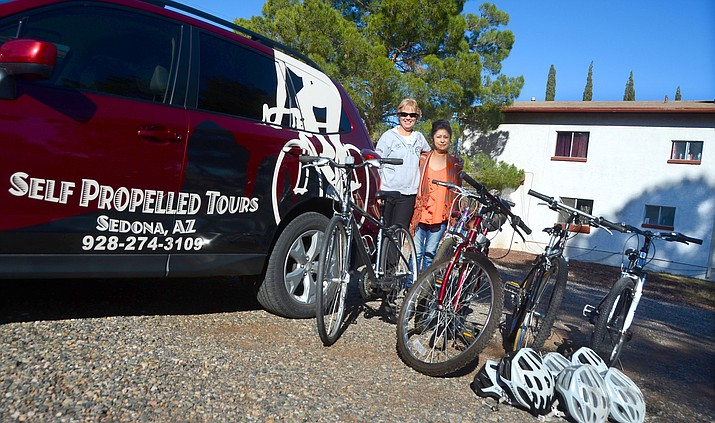 Heather Parris of Self Propelled Tours in Sedona and Angie Lozano unload bikes donated by Parris in front of Angie's House. VVN/Vyto Starinskas
