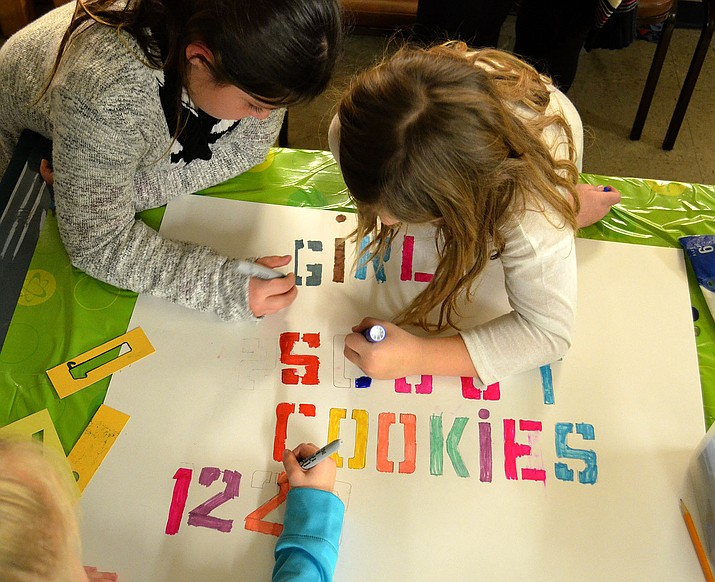 Girl Scouts color a sign for their cookie booth at Katherine Heidenreich Adult Center Thursday night.