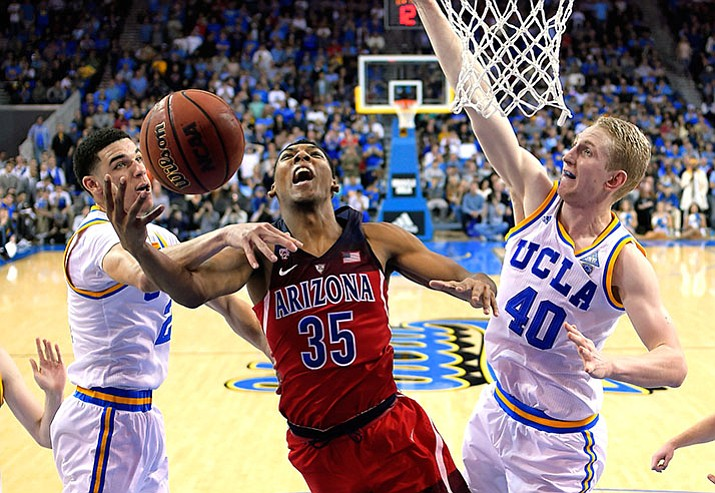 Arizona guard Allonzo Trier, center, shoots as UCLA guard Lonzo Ball, left, and center Thomas Welsh defend during the second half of an NCAA college basketball game, Saturday, Jan. 21, in Los Angeles. Arizona won 96-85.