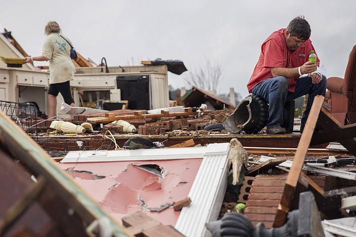 Jeff Bullard sits in what used to be the foyer of his home as his daughter, Jenny Bullard, looks through debris at their home that was damaged by a tornado, Sunday, Jan. 22, in Adel, Ga.