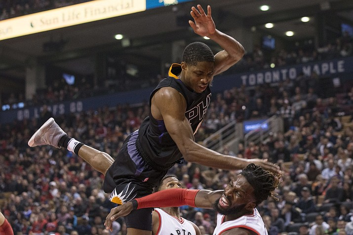 Phoenix Suns' Brandon Knight, top, fouls Toronto Raptors' DeMarre Carroll during first-half of Sunday's NBA basketball game in Toronto.