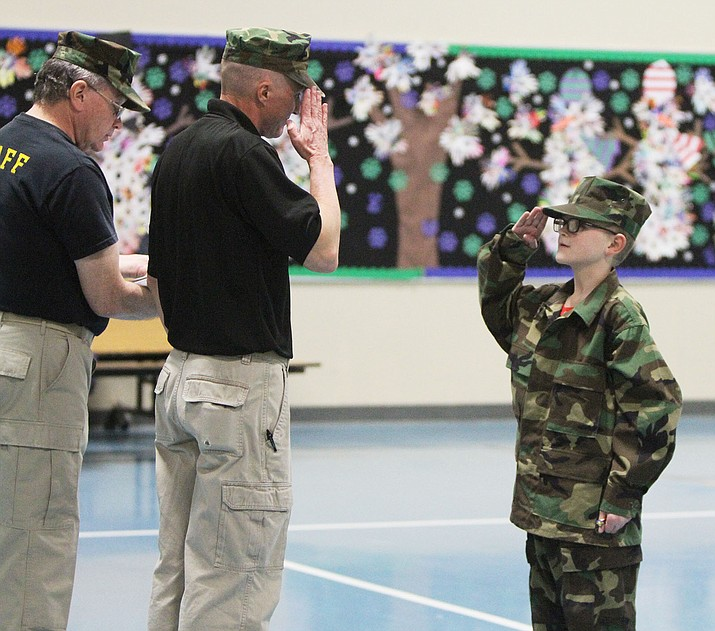 """Robert Johnson, 11, salutes as he is awarded """"Most Improved"""" during a Young Marines ceremony for Boot Camp graduates at Kingman Academy of Learning Thursday night. Jim Glover, Unit Executive Officer (left), and Robert Skankey, Unit Commander, present the award."""