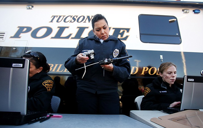Officer Monica Vannorman, center, photographs a pistol as officer Merri Hughes, right, logs the relinquished weapons at a gun buyback event in 2013 at the Tucson Police Department Midtown Substation. Gun owners waited in lines over an hour to relinquish their handguns and rifles in exchange for a $50 Safeway gift card.