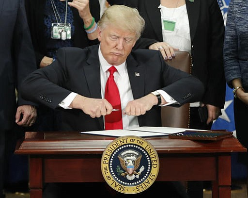 President Donald Trump takes the cap off a pen before signing executive order for immigration actions to build border wall during a visit to the Homeland Security Department in Washington, Wednesday, Jan. 25, 2017.