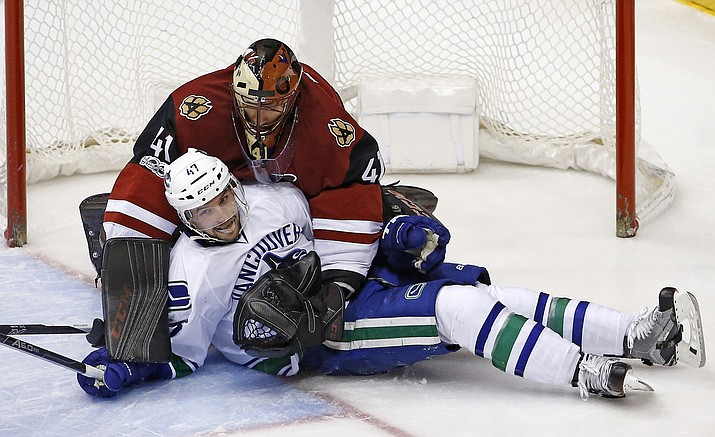 Vancouver Canucks left wing Sven Baertschi (47) crashes into Arizona Coyotes goalie Mike Smith (41) during the second period Thursday, Jan. 26, in Glendale. (Ross D. Franklin/Associated Press)