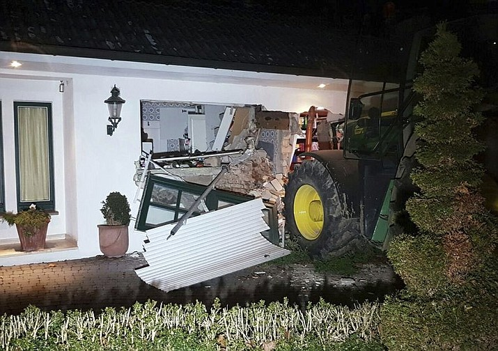 A tractor stands in front of a damaged house after it broke through the wall in Buende, north-western Germany, Thursday, Jan. 26, 2017. Unknown intruders steered the tractor into the house and broke through the wall in order to steal a safe. The residents were not injured.