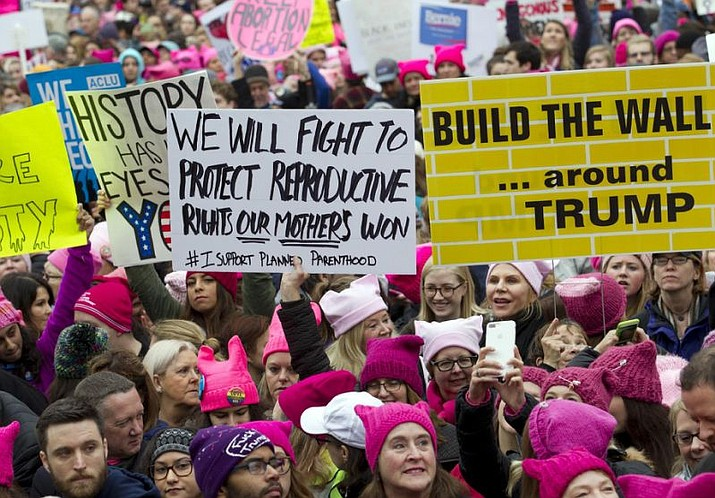 FILE - In this Saturday, Jan. 21, 2017 file photo, women with bright pink hats and signs begin to gather early and are set to make their voices heard on the first full day of Donald Trump's presidency, in Washington. The owner of a Tennessee knitting store doesn't want anyone buying its yarn for arts and crafts for the women's movement, following weekend protests by marchers in knitted, pointy-eared hats. The Tennessean newspaper reported that the comments Tuesday on the Facebook page of The Joy of Knitting store in Franklin drew both support and vows of a boycott.