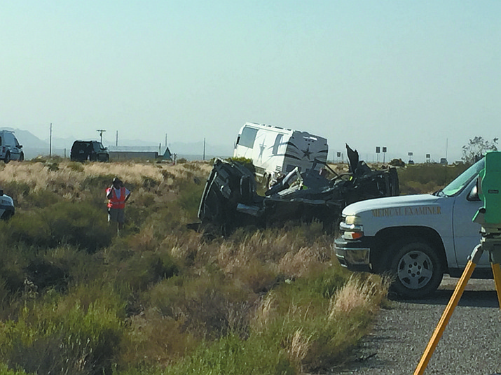 A Dallas Cowboys bus is upright next to another vehicle that carried four people who were killed on U.S. 93 about 30 miles north of Kingman in July.