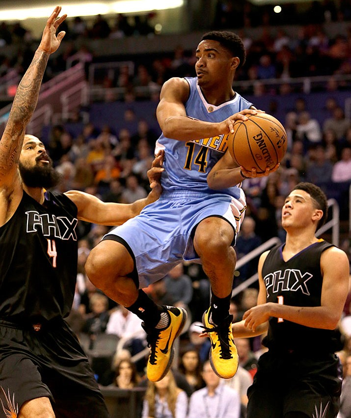 Denver Nuggets guard Gary Harris (14) drives between Phoenix Suns center Tyson Chandler (4) and Devin Booker in the first quarter during an NBA basketball game, Saturday, Jan. 28, in Phoenix.
