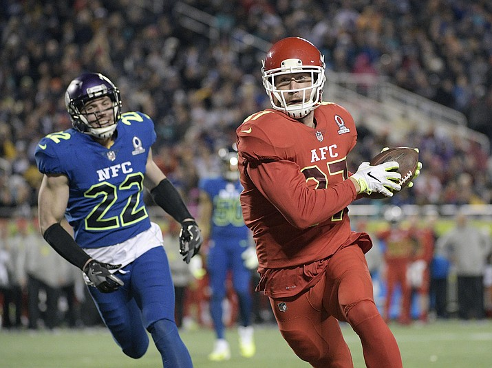 AFC tight end Travis Kelce (87), of the Kansas City Chiefs, runs into the enzone for a touchdown ahead of NFC free safety Harrison Smith (22), of the Minnesota Vikings during Sunday's NFL Pro Bowl football game in Orlando, Fla.