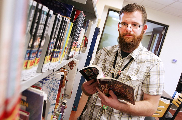 """Everybody who is a young adult librarian does it because they genuinely like making a difference in other people's lives,"" says Zack Garcia, Camp Verde's new teen librarian. (Photo by Bill Helm)"