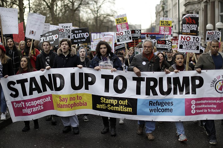 People hold a banner as they take part in a protest march in London, against U.S. President Donald Trump's ban on travelers and immigrants from seven predominantly Muslim countries entering the U.S., Saturday, Feb. 4. Thousands of protesters have marched on Parliament in London to demand that the British government withdraw its invitation to U.S. President Donald Trump.