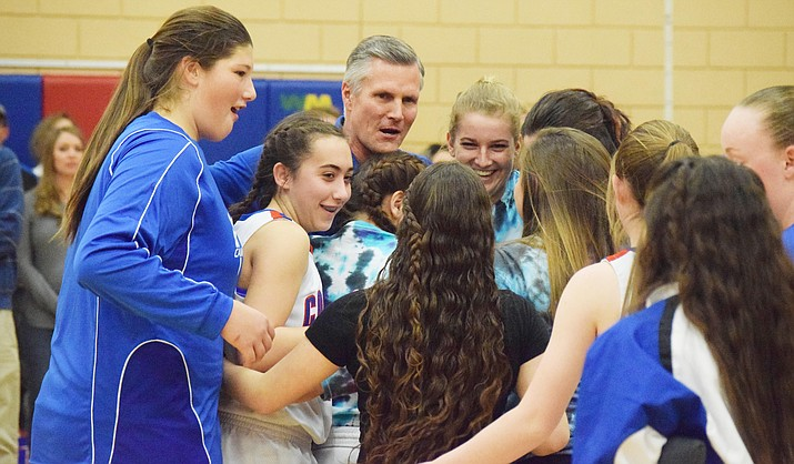 Camp Verde girls basketball head coach Mark Showers shares a group hug with the current Lady Cowboys on Friday. After the 54-11 Senior Night win over Northland Prep, Camp Verde honored Showers. (Photo by James Kelley)