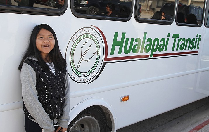 Sunny Wakayuta, 11, stands in front of a new Hualapai Transit bus. She designed the logo she stands next to. She tied with Craig Talieje in a design contest. Her work is the new logo and his work will be the wrap-around artwork expected to soon be placed on the buses.