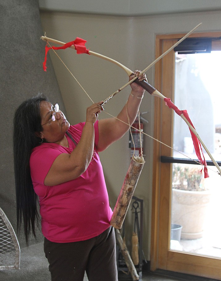 Bonita Imus uses a bow and arrow to teach students the Hualapai words related to the bow, arrow, and other objects. The tribe is passing on its heritage and customs to its youth.